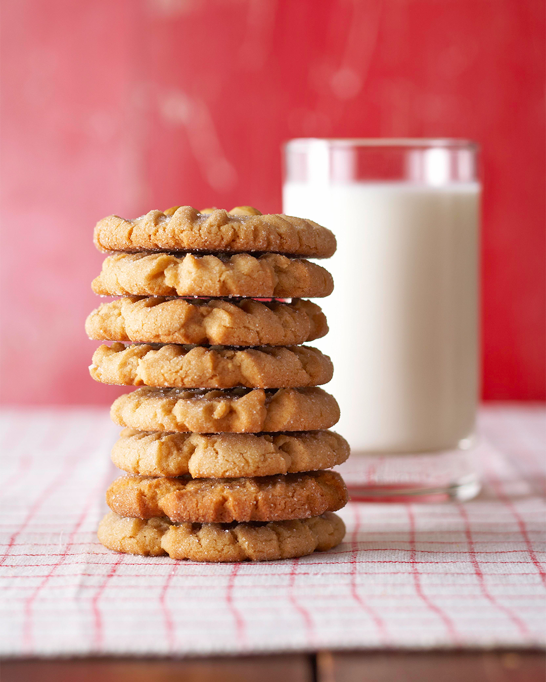 Peanut Butter Cookies in a stack with a glass of milk