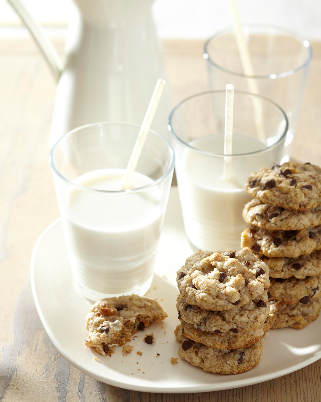 Whole Grain Chocolate Chip Cookies in stacks with milk
