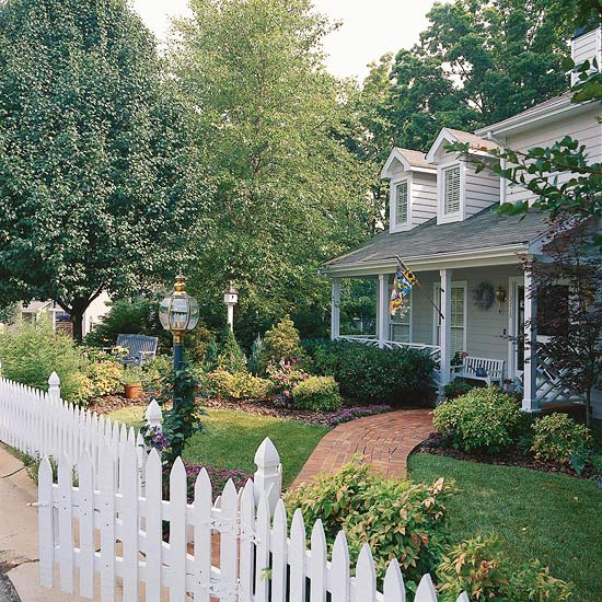 White Cape Cod house with picket fence and brick walkway