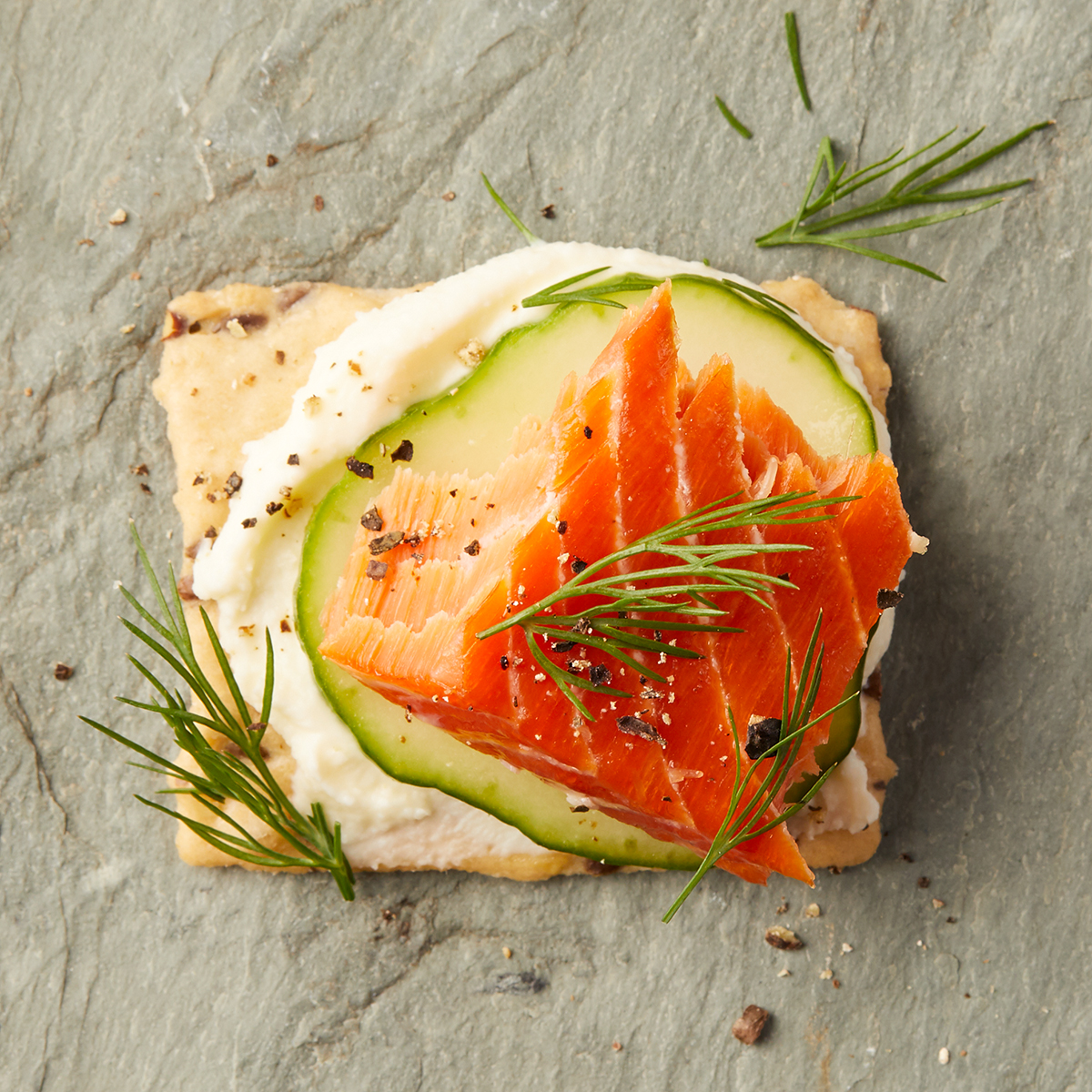 Cracker with crème fraiche, cucumber, smoked salmon, dill, and cracked pepper