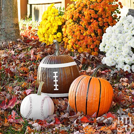 pumpkins in leaves painted as baseball, basketball and football