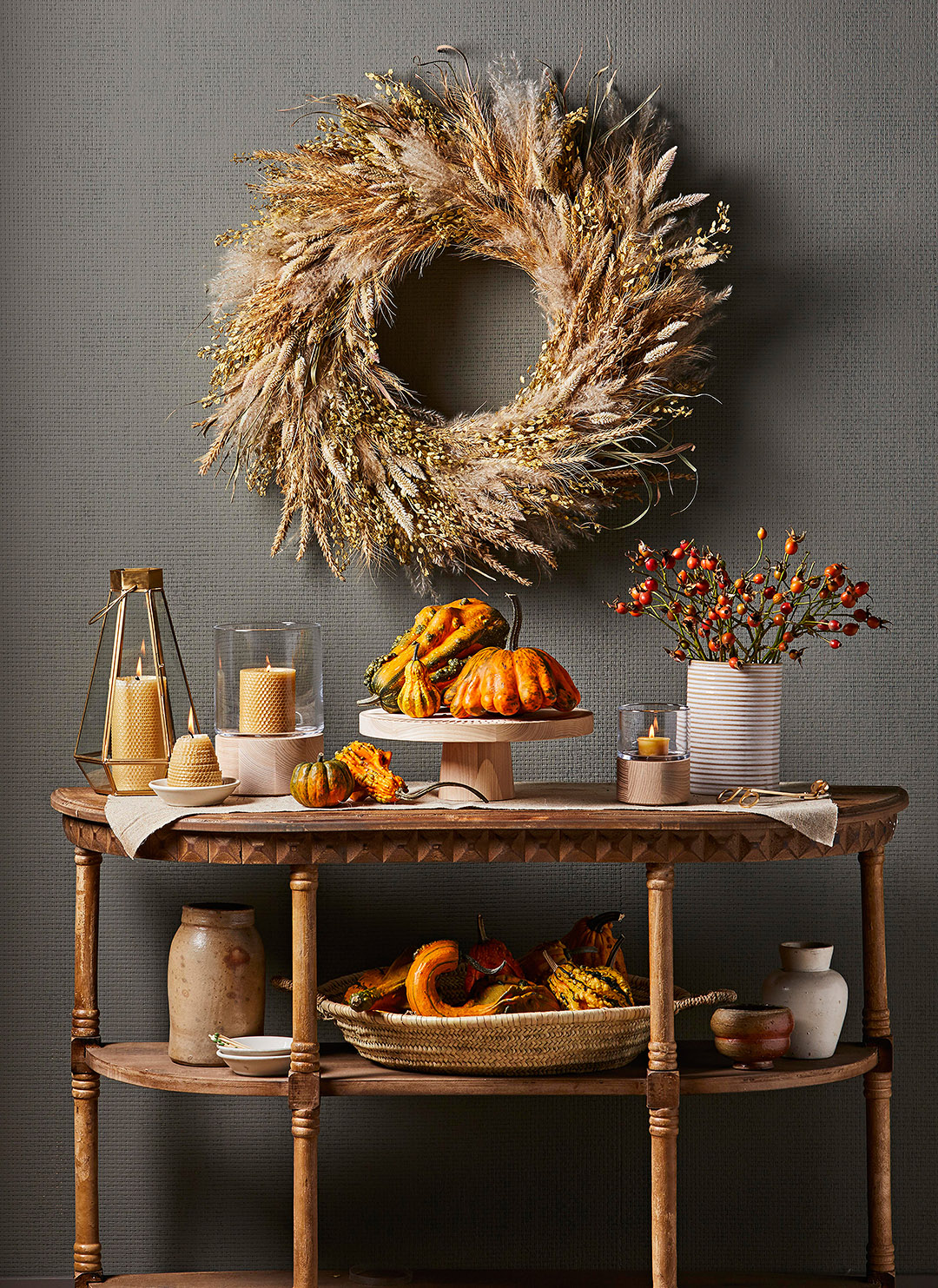 side table decorated for fall with gourds large wreath hanging above