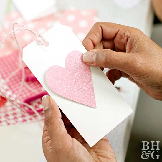 woman holding glitter heart tag