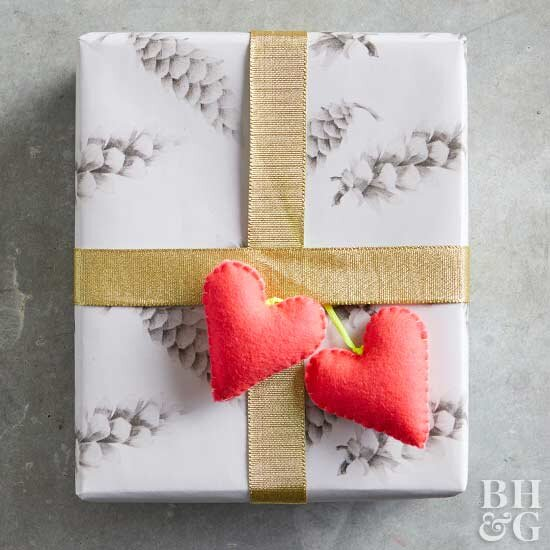 wrapped gift with gold ribbon and heart topper