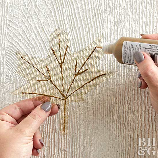 applying gold paint to leaf