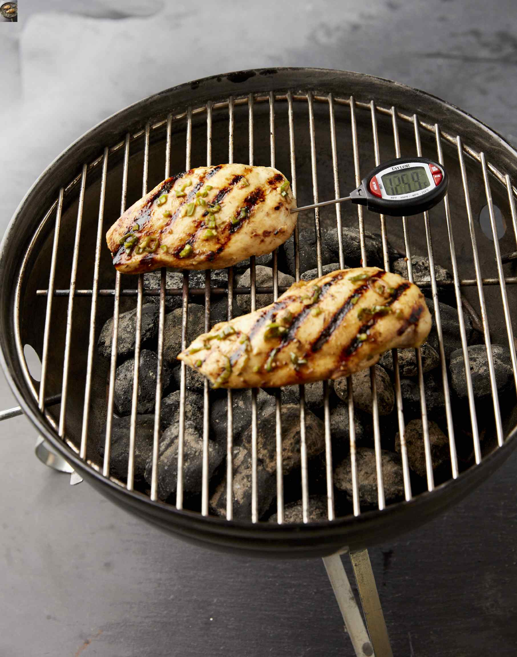 digital instant-read thermometer in cooked chicken breast on the grill