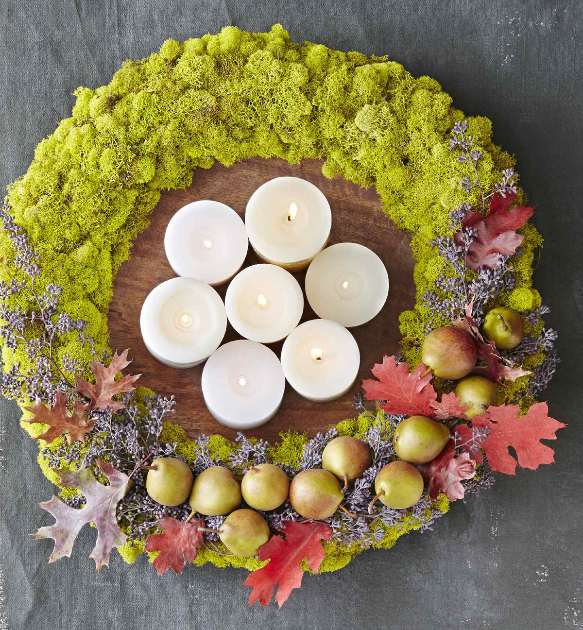 DIY green moss wreath used as seasonal centerpiece on table with candles