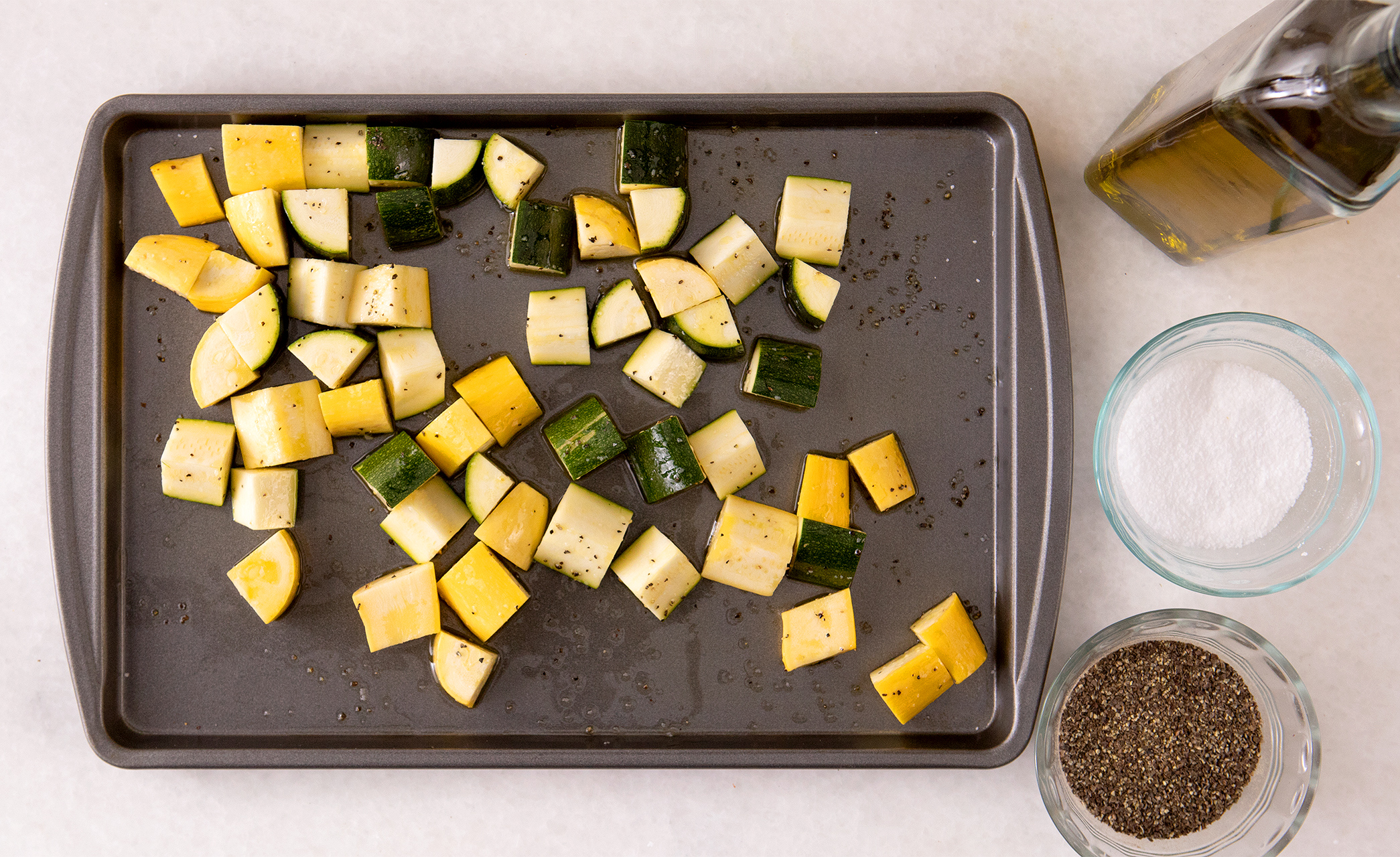 yellow squash and zucchini on pan with oil salt pepper to roast