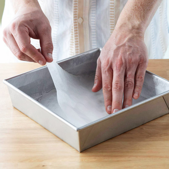 Fitting waxed paper into the pan