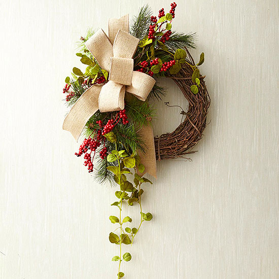 adding greenery and berries to grapevine wreath
