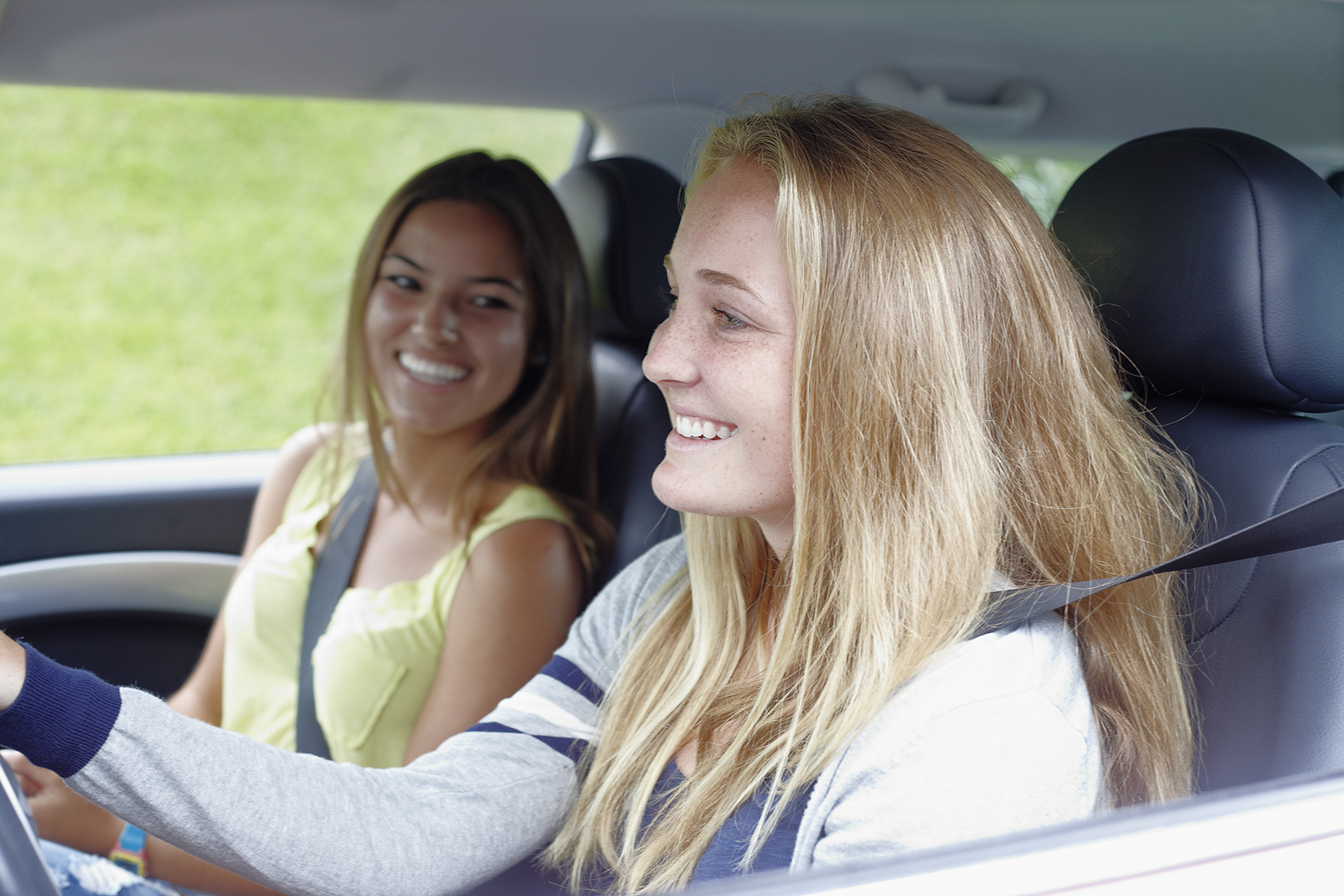 two teenage girls driving in a car