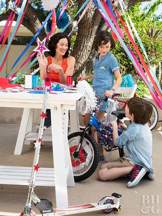 boy decorating bike with mom sister