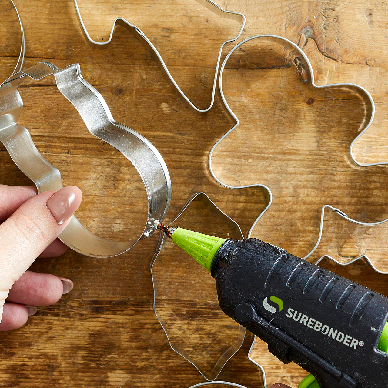 applying hot glue to christmas cookie cutters
