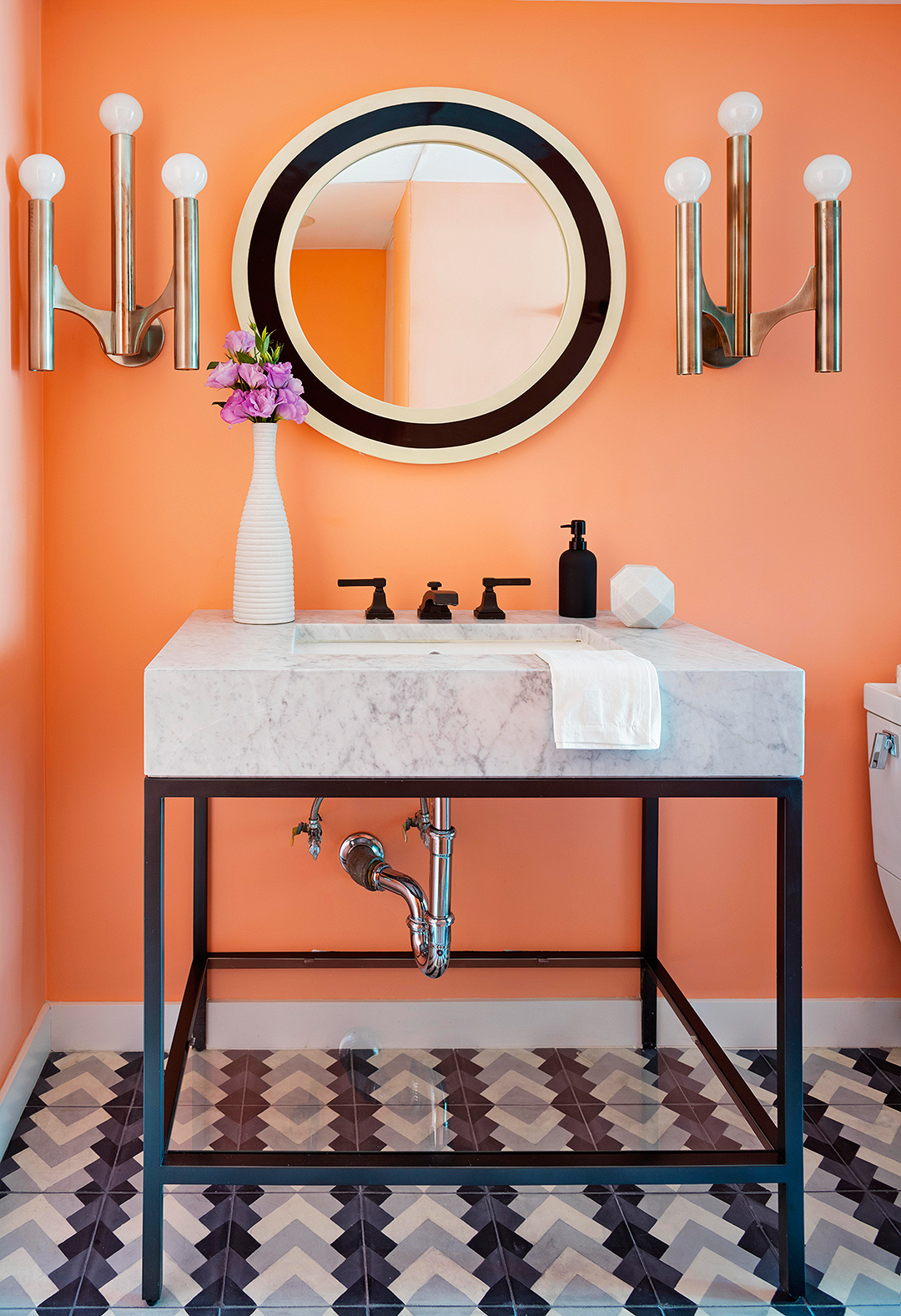 orange painted bathroom with marble stone sink modern light fixtures and round mirror