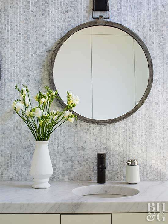 bathroom sink, round bathroom mirror, flowers in vase