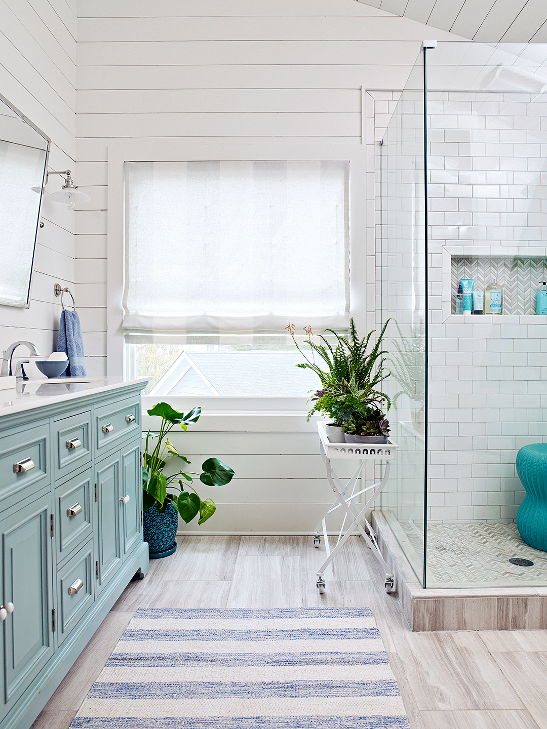 walk in shower in white and seafoam bathroom with plants