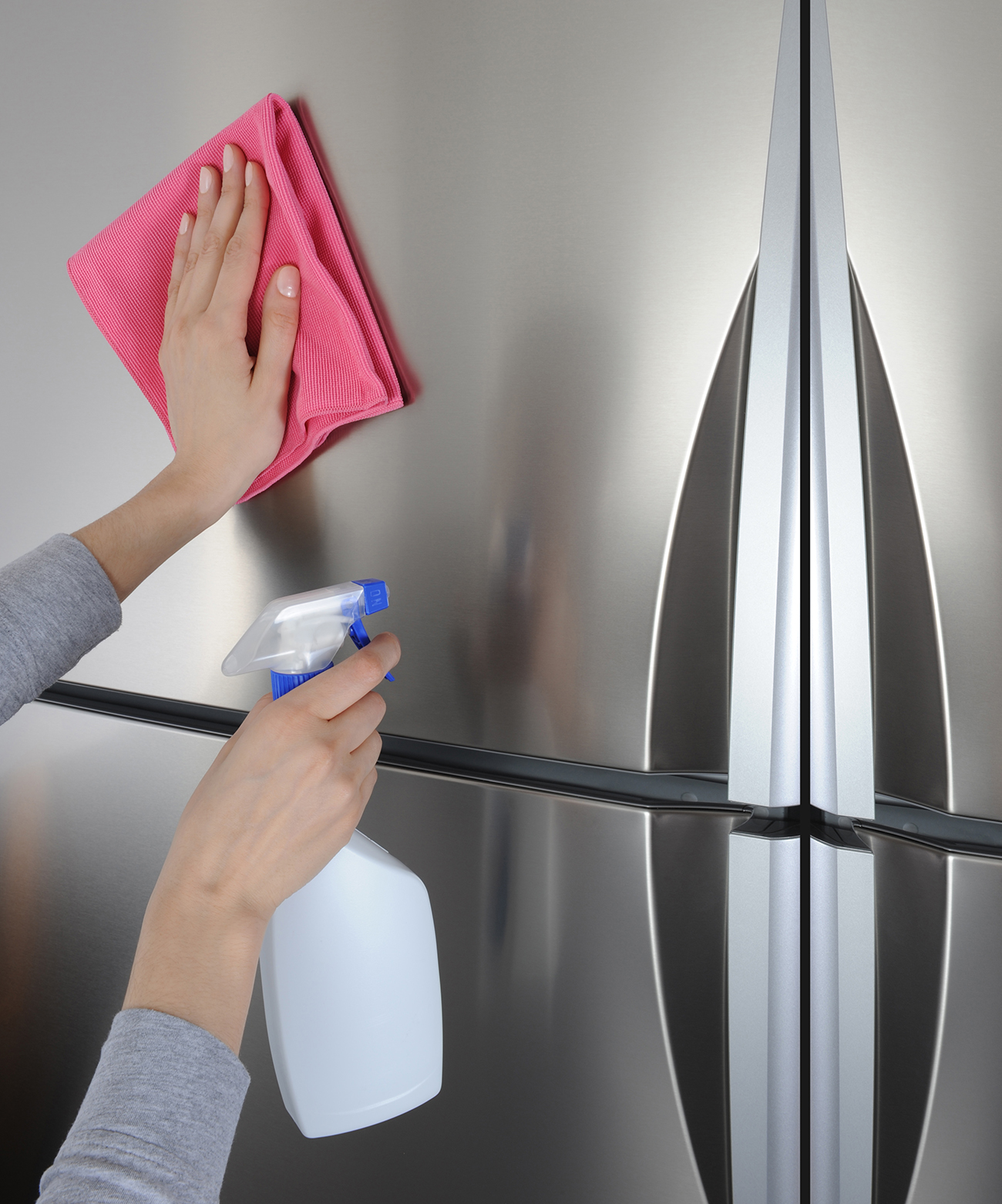 cleaning stainless-steel fridge with microfiber cloth