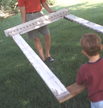 Man and boy carrying a window frame trellis during construction