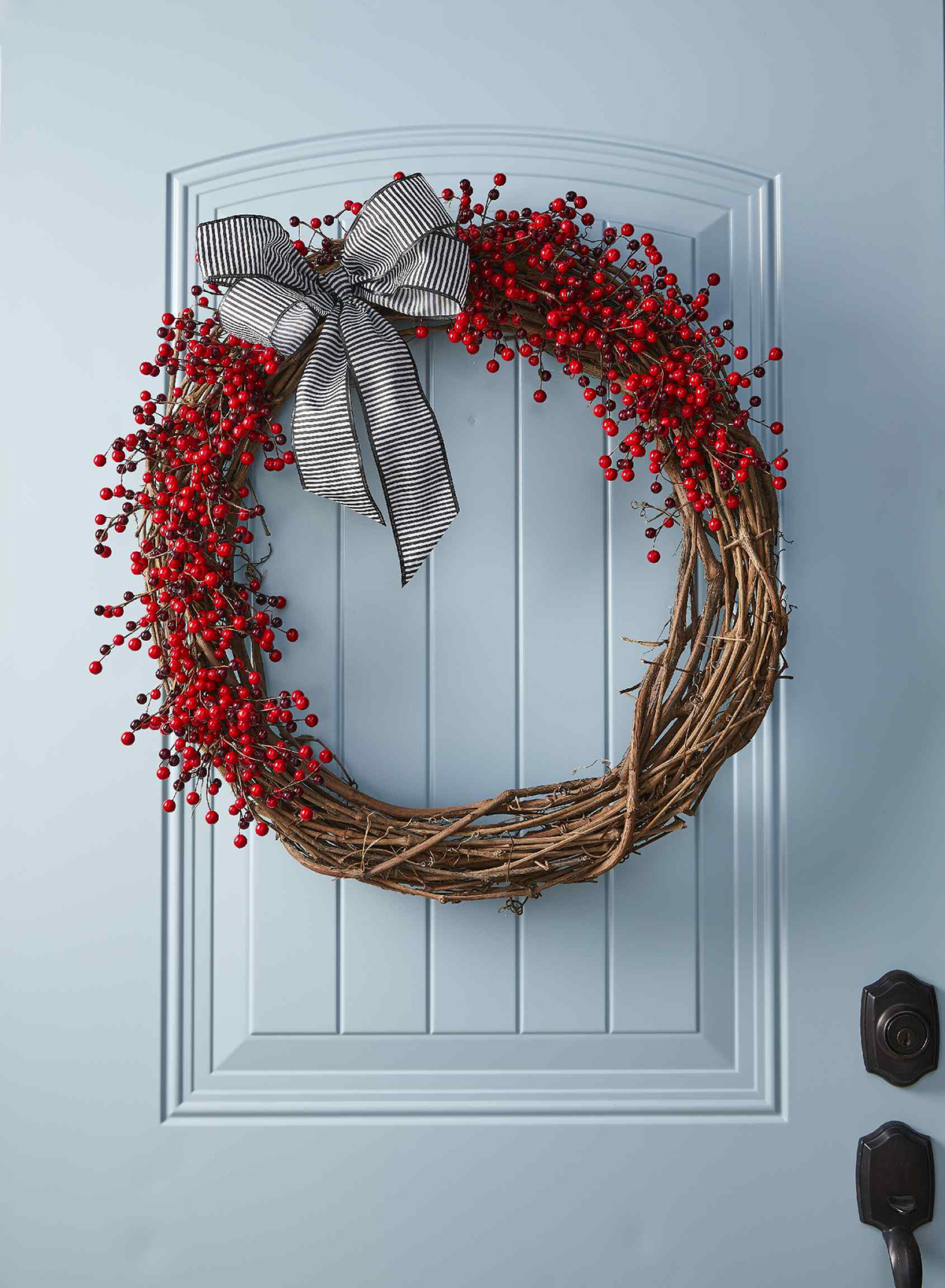 berry and wood wreath with bow on blue door