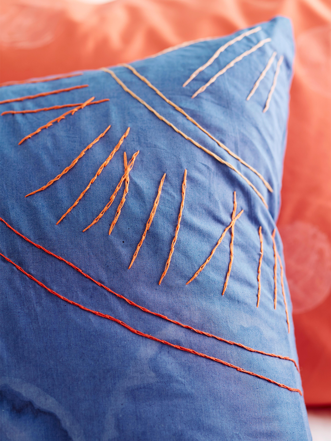 blue pillow with orange stitching