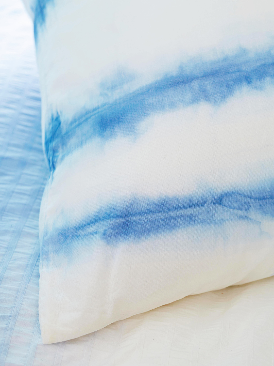 blue and white striped dyed pillow on comforter