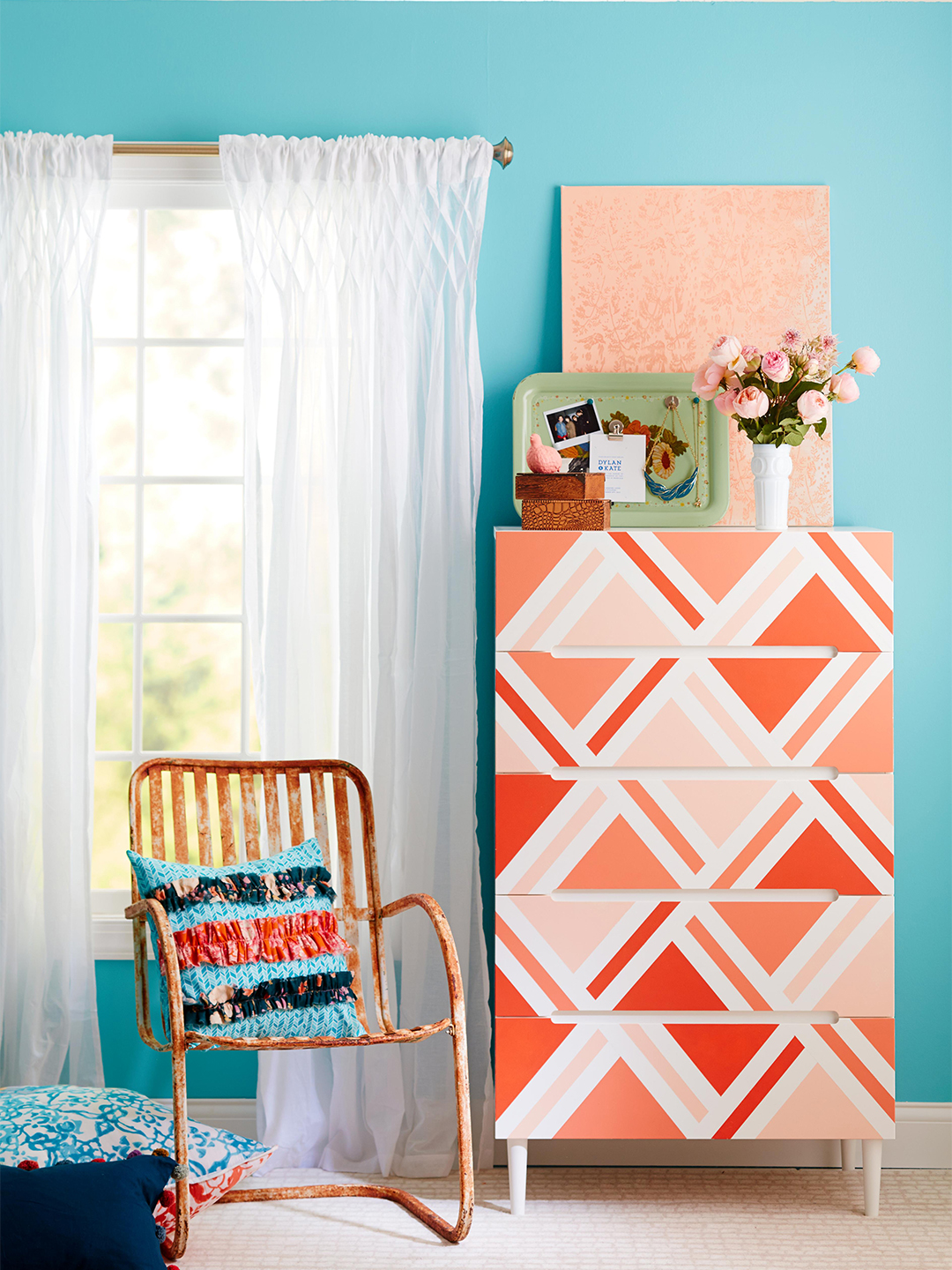 orange and white geometric dresser in teal bedroom