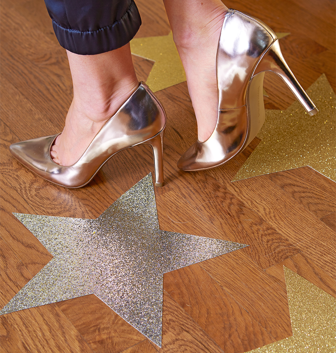 walk way of metallic stars on floor with woman in shiny high heels