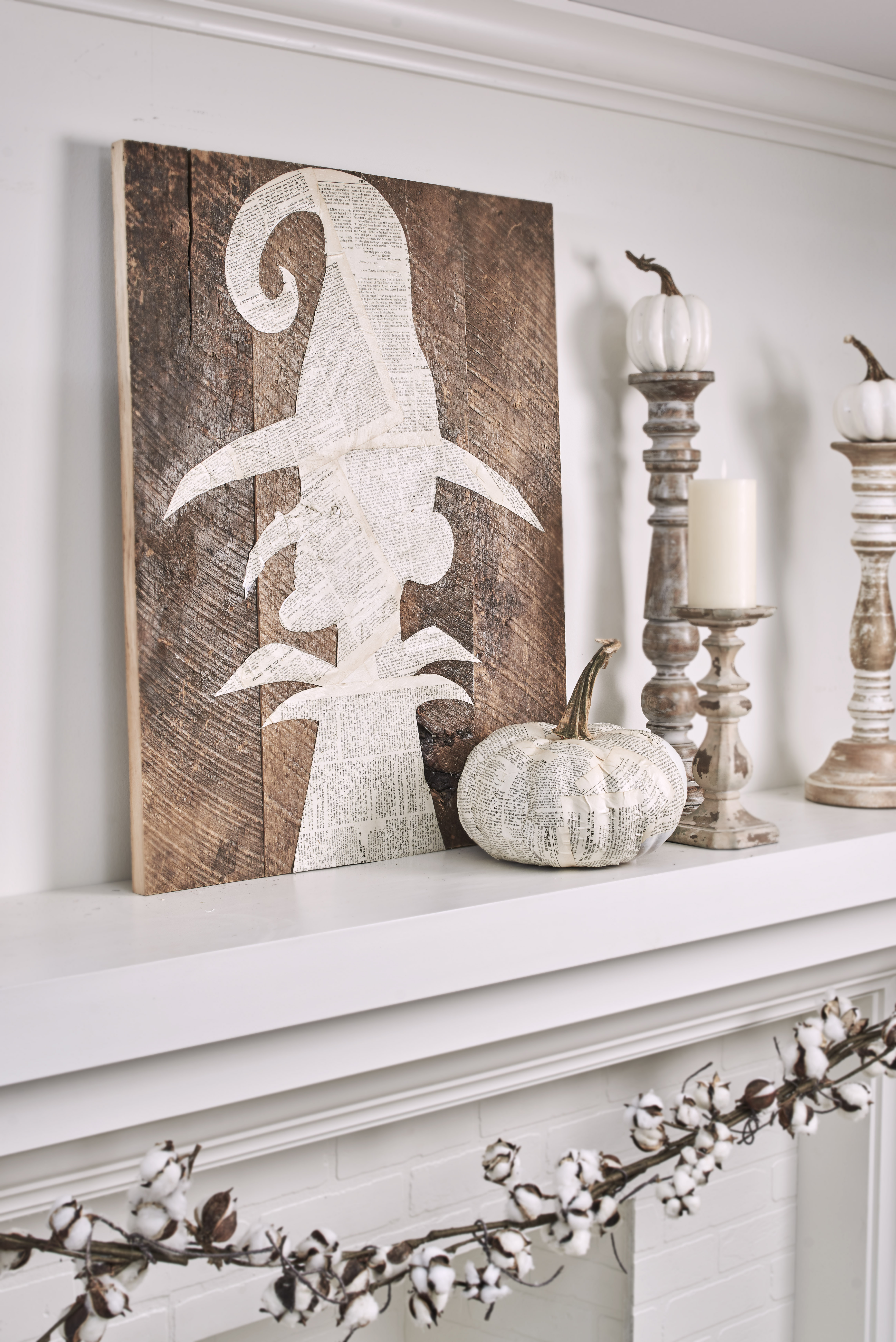 brown wood sign with a white witch painted on it, sitting on a white mantel