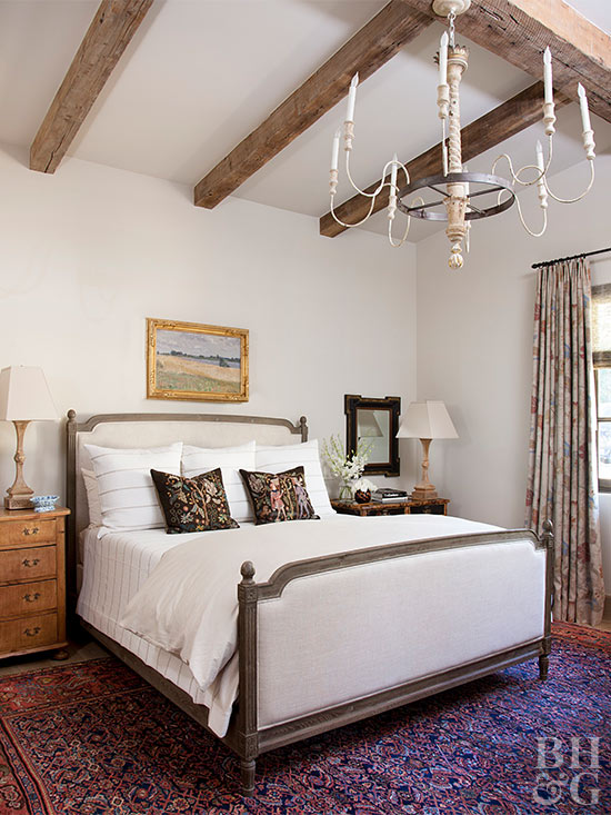 White bedroom with wood beam vaulted ceiling
