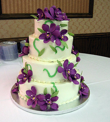 Four tier cake with purple sugar flowers leaves and stems