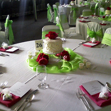Mini cake on reception table with pink flowers and green fabric underneath