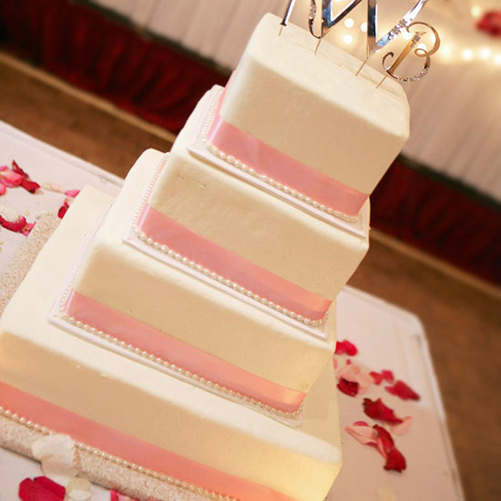 white cake with pink ribbon