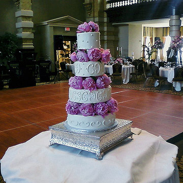 Four tier white cake with peonies between each layer