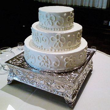 Three tier white cake with daisy pattern