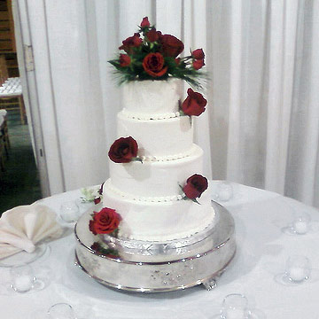 White four tier cake with real red roses