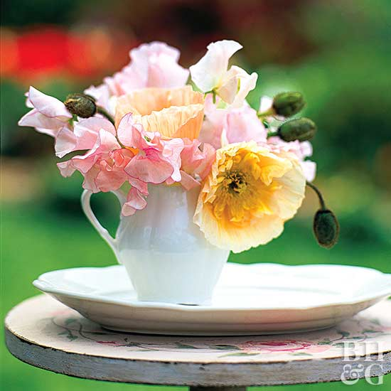 Poppies and sweet peas in a white creamer