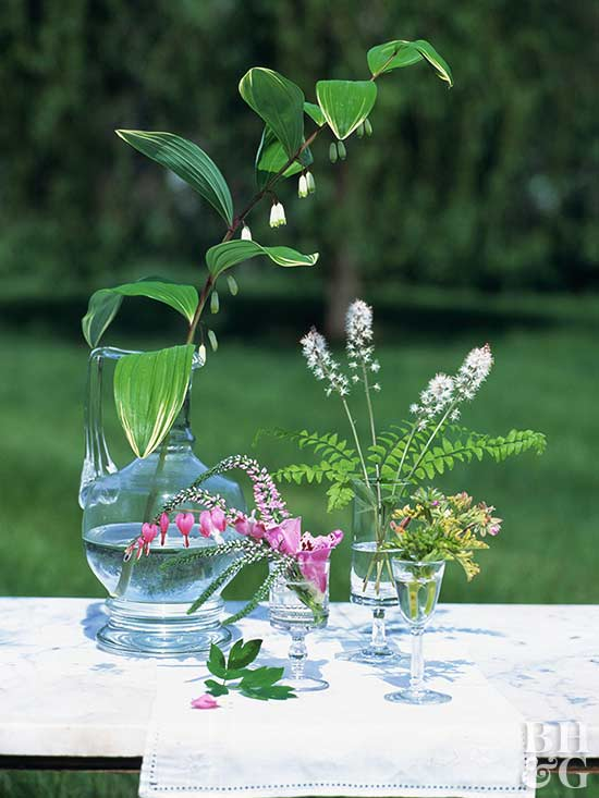 Stems of various flowers in their own containers arranged together
