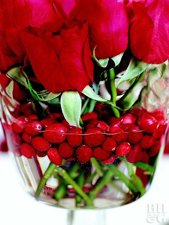 Cranberries floating in water of vase and rose stems