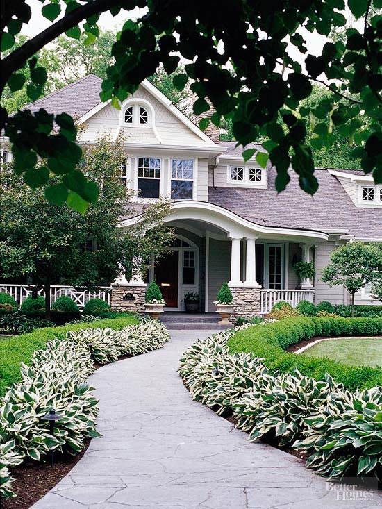 Front entrance to house, sidewalk lined with hostas and shrubs