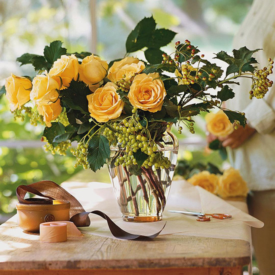 yellow roses in vase ribbons lady behind