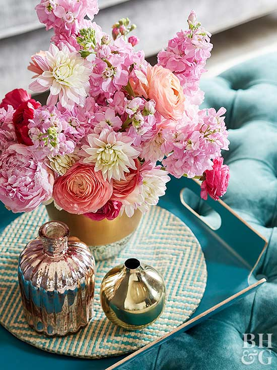 Three gold vases on decorative tray with pink bouquet of flowers