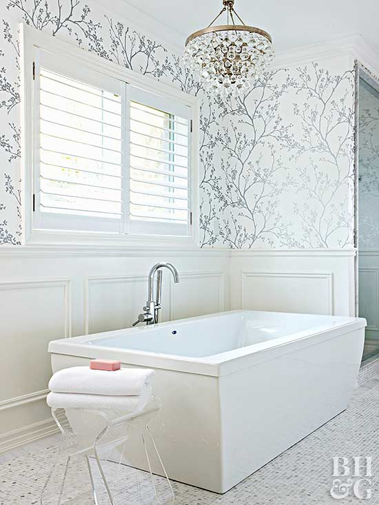 white bathroom with large white tub and neutral floral wallpaper