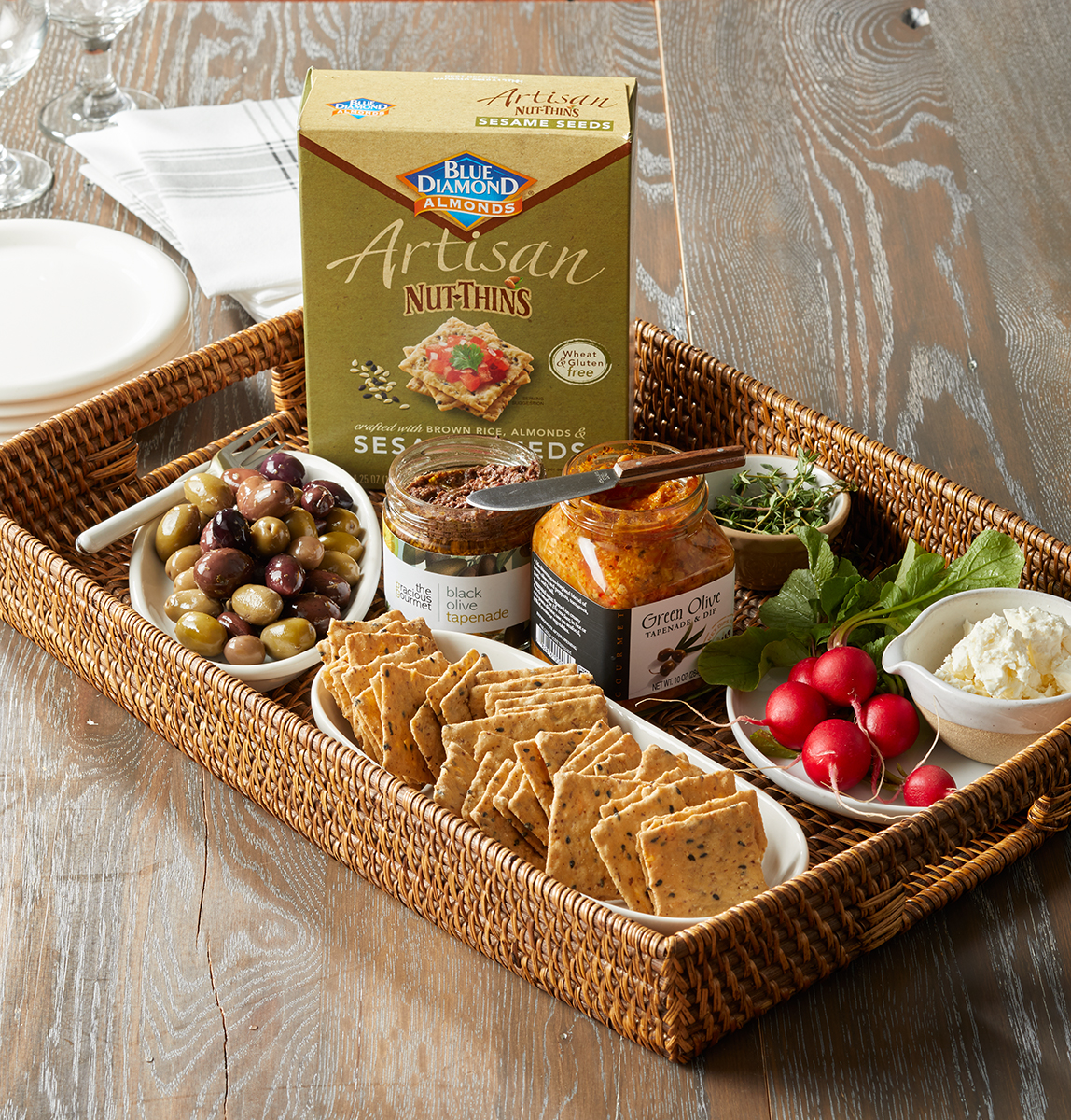 wicker tray with dishes of snacks artisan nut-thins and spreads