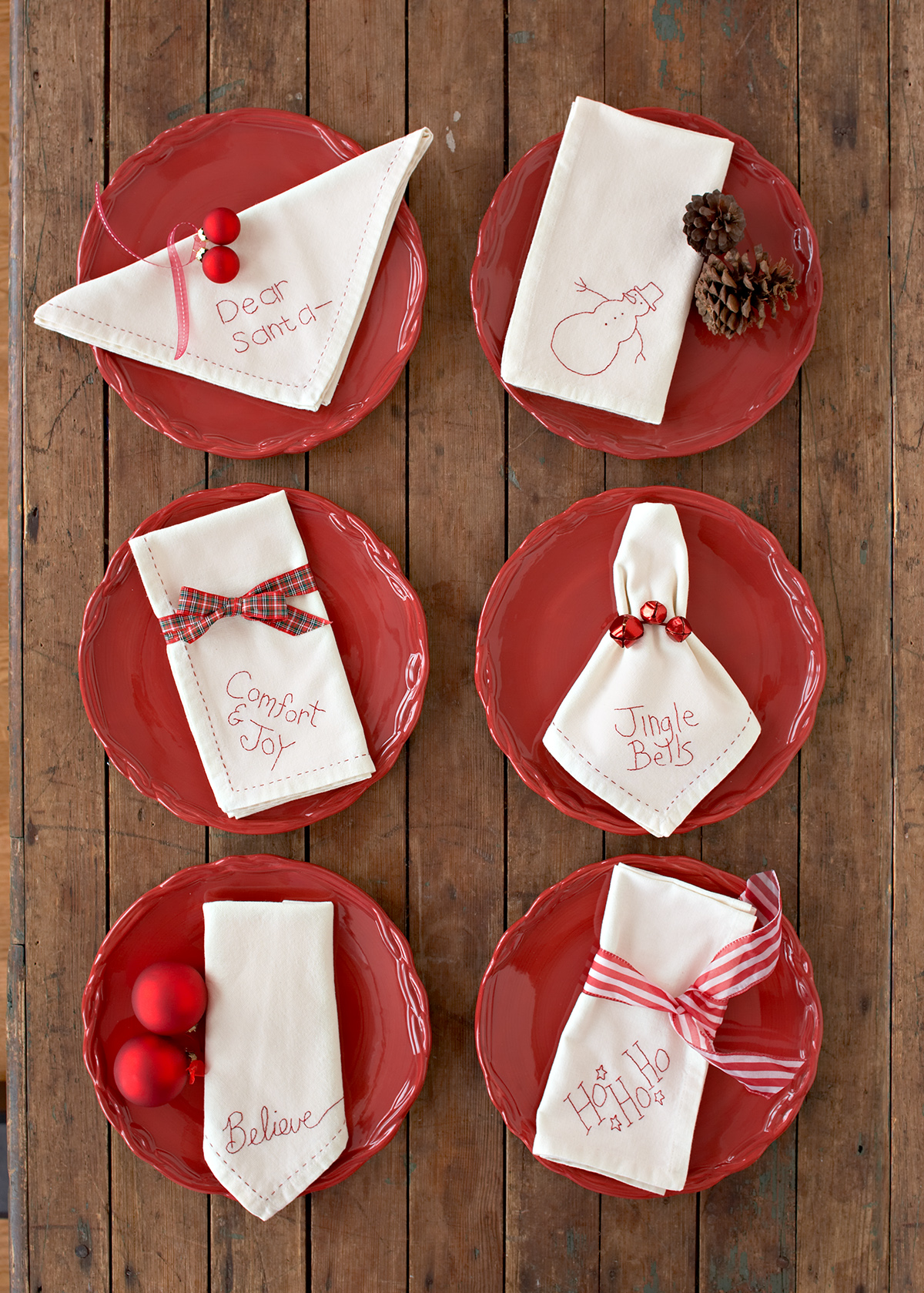 red plates with white napkins embroidered with various holiday sayings