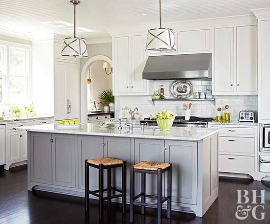 kitchen with white cabinets dark wood floors and grey painted island