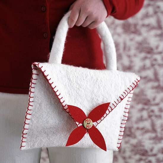 Close up of little girl holding out white felt purse with a felt poinsettia on it