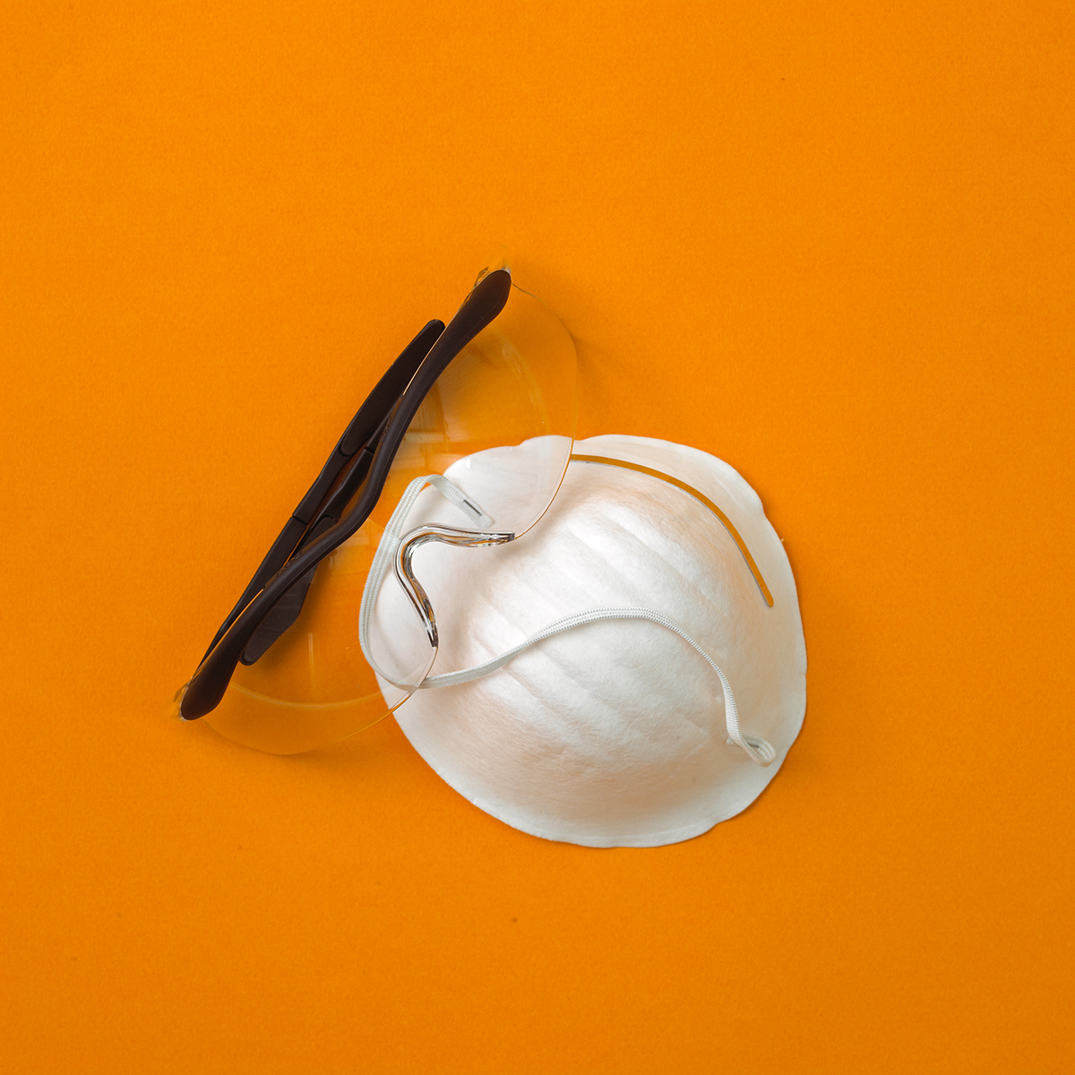 dust mask and safety glasses on orange background
