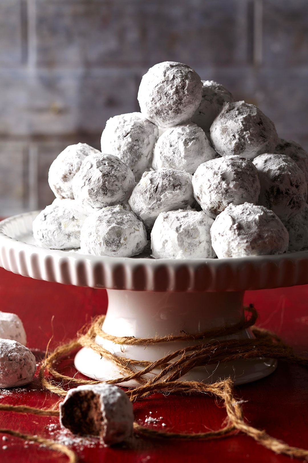 Chocolate Snowball Cookies covered in powdered sugar on pedestal