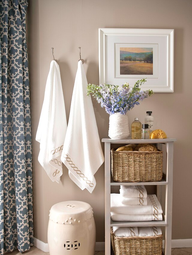 Soft Taupe Bathroom With White Towels Hanging And Folded On Shelf