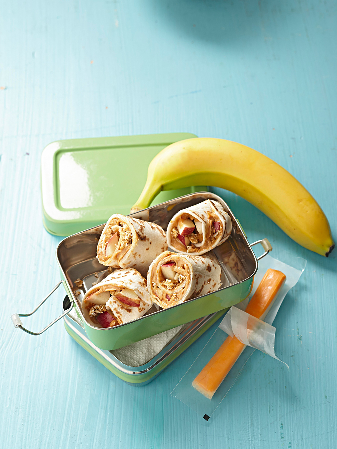 crunchy peanut butter and apple wrap in lunch box with banana and cheese stick